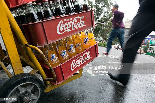 A worker pushes a hand truck with CocaCola products while making deliveries in Mexico City Mexico on Thursday Sept 5 2013 CocaCola Femsa SAB a...