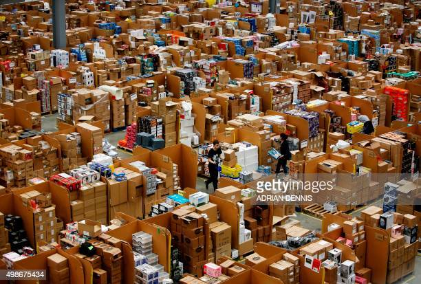 A worker pushes a trolley as he walks between goods stored inside an Amazoncouk fulfillment centre in Hemel Hempstead 25 November 2015 Shops could be...