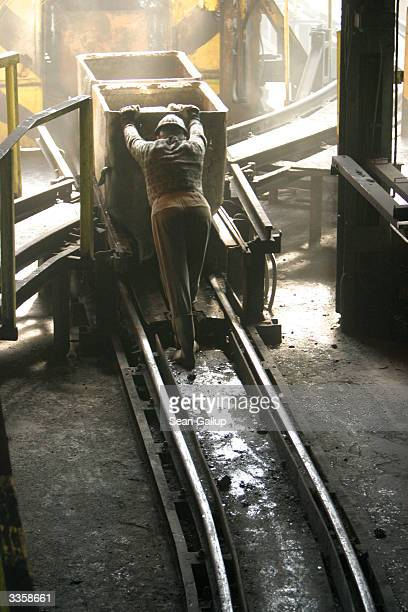 A worker pushes a wagon loaded with freshlymined high quality coal at the Wieczorek coal mine April 14 2004 in Katowice Poland Poland will be the...