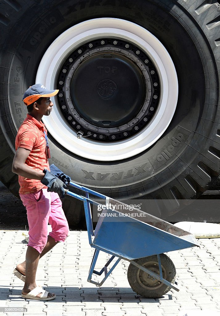 A worker pushes a wheelbarrow past a giant wheel of an oversized vehicle on display at the venue for the 'Make in India' showcase week in Mumbai on February 11, 2016. Over 190 companies, including national conglomerates and multinational corporations, 5,000 delegates from 60 countries, and leading industrialists including Ratan Tata and Mukesh Ambani will be participating in the maiden 'Make in India' showcase to be held in Mumbai from February 13-18. AFP PHOTO/ INDRANIL MUKHERJEE / AFP / INDRANIL MUKHERJEE