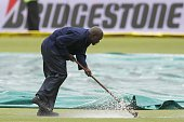 A worker pushes away water with a broom off the playing field preparing it for the umpire's inspection during the 2nd day of the second test match...