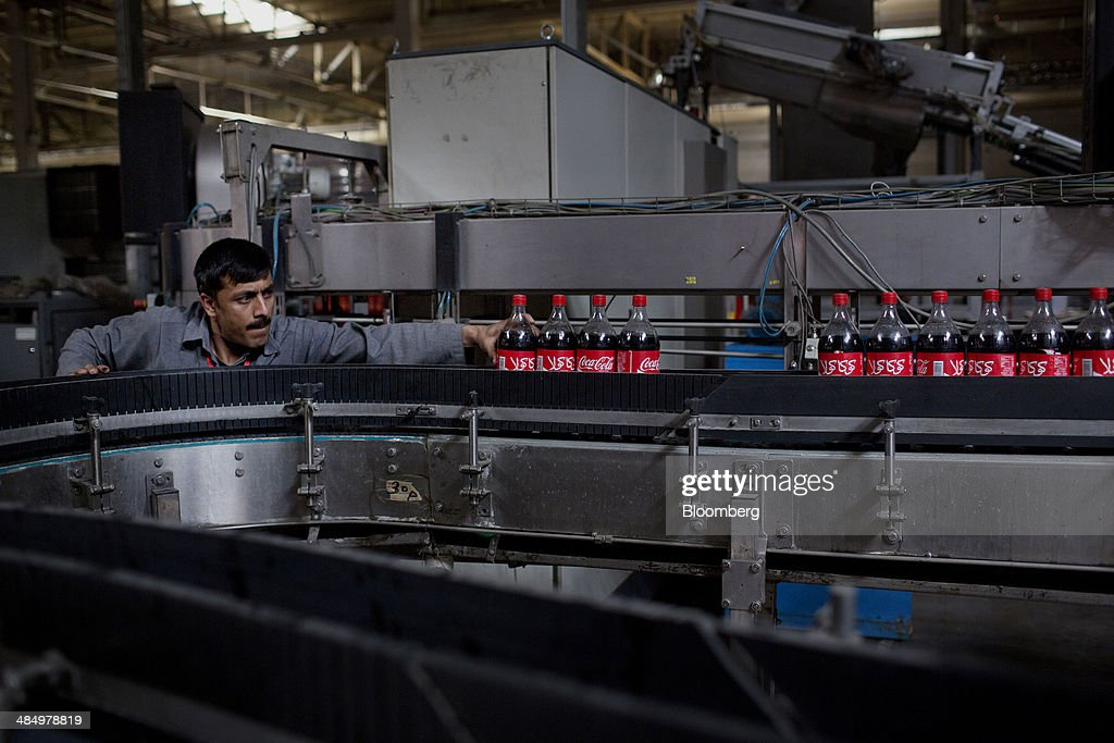 A worker pushes bottles of Coca-Cola Co. beverage along a production line at the Habib Gulzar Non-Alcoholic Beverage Ltd. bottling facility in Kabul, Afghanistan, on Thursday, April 10, 2014. Coca-Cola Co., the world's largest soda maker, today showed signs of a rebound in the first three months of the year, easing the concerns that arose when the company unsettled investors with surprisingly sluggish global sales in the fourth quarter. Photographer: Victor J. Blue/Bloomberg via Getty Images