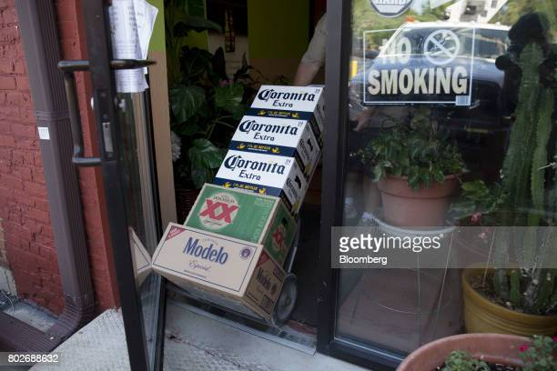 A worker pushes cases of Constellation Brands Inc Corona and Modelo beer into a restaurant during a delivery in Ottawa Illinois US on Tuesday June 27...