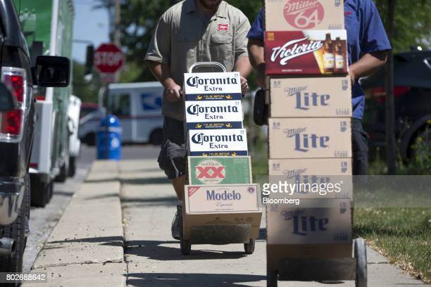A worker pushes cases of Constellation Brands Inc Corona and Modelo beer during a delivery in Ottawa Illinois US on Tuesday June 27 2017...