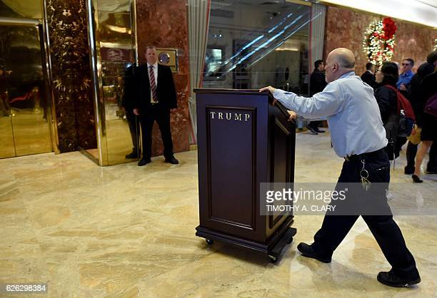 A worker pushes in a podium to Tump Tower during another day of meetings for Presidentelect Donald Trump on November 28 2016 in New York / AFP /...