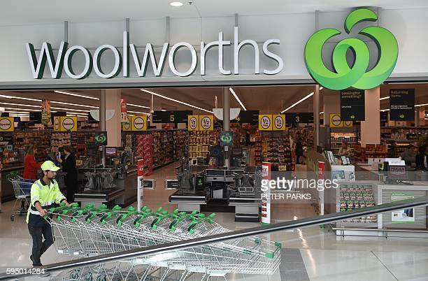 A worker pushes shopping trollys at a Woolworths store in Sydney on August 25 2016 Australian supermarket giant Woolworths on August 25 reported a...