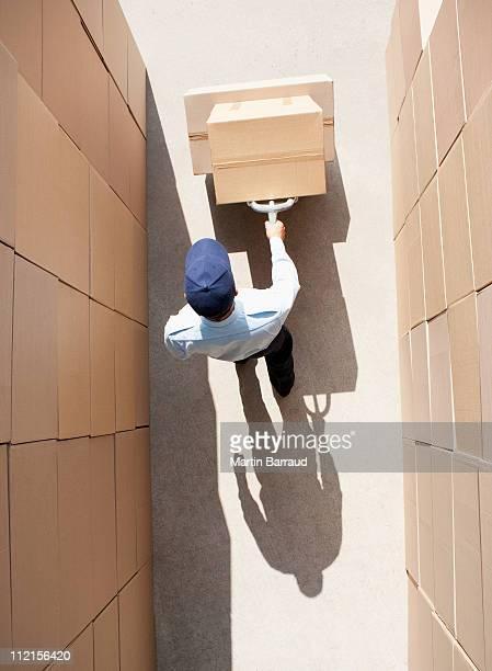 Travailleur en poussant le diable boîtes
