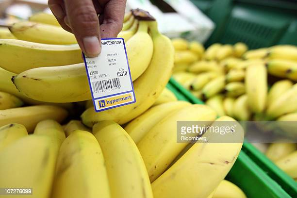 A worker puts a price tag on bananas in the produce section of PT Matahari Putra Prima's Hypermart hypermarket in Jakarta Indonesia on Friday Dec 3...