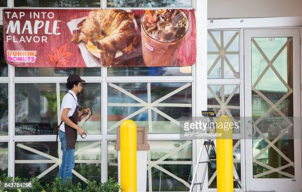 A worker puts tape on windows at a Dunkin Donuts store during preparations for Hurricane Irma in Miami Florida September 7 2017 Miami orders people...
