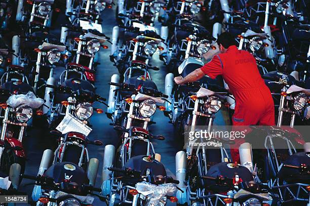 A worker puts the final touches on a fully produced Ducati 'Monster' at the Ducati factory September 12 2002 in Borgo Panigale Bologna Italy Ducati...
