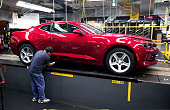 GM worker puts the finishing touches on a new General Motors 2016 Chevrolet Camaro as it rolls off the production line at GM's Lansing Grand River...