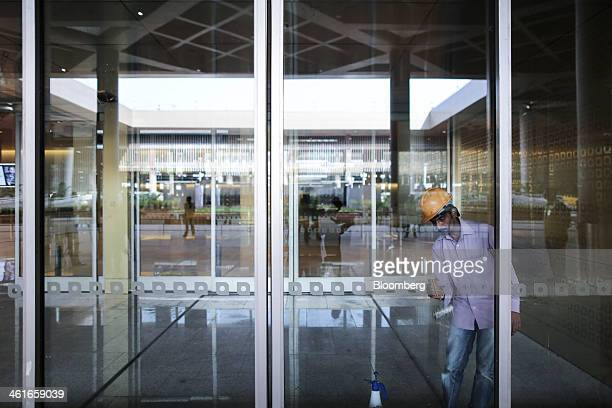 A worker puts the finishing touches to a glass sliding door inside the newly built Terminal 2 of the Chhatrapati Shivaji International Airport...