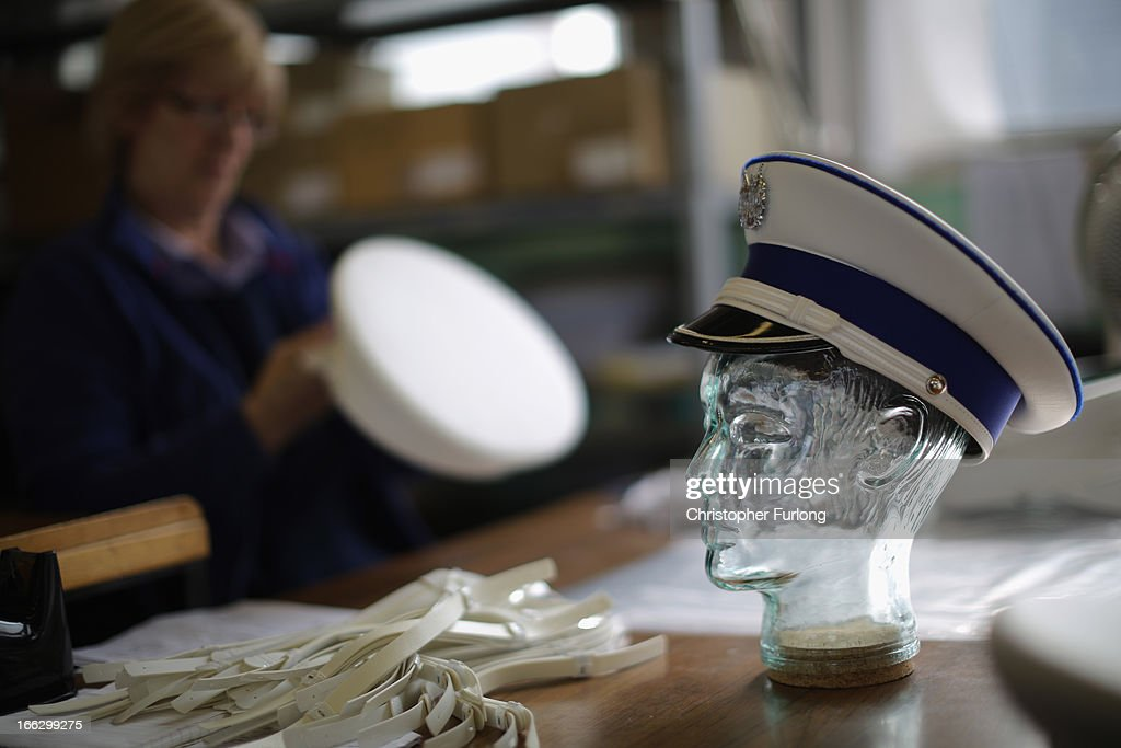 A worker puts the finishing touches to military hats at civil and military regalia manufacturers Toye, Kenning And Spencer on April 10, 2013 in Bedworth, England. Toye, Kenning And Spencer are the oldest fraternal regalia manufacturers in the world and were established in 1685. From their factories in Birmingham and Bedworth the company's experts in weaving, gold silversmithing, enamelling and embroidery create a vast array of regalia from civilian and military life.