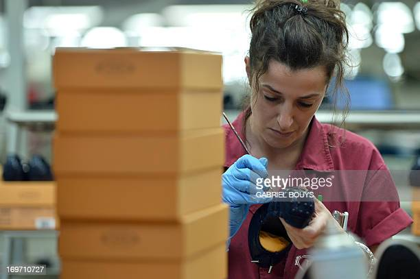 A worker puts the last touch on a shoe in the factory of the Italian shoes and luxury leather goods Tod's on May 28 2013 at the headquarters of the...