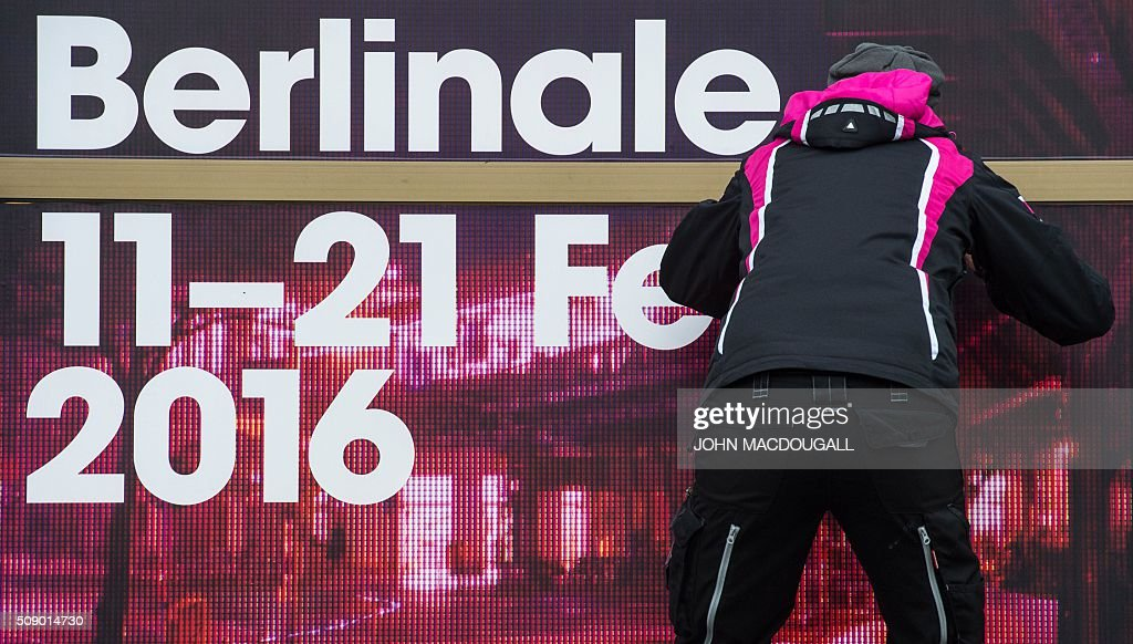 A worker puts up a poster advertising the Berlinale Film Festival at the Friedrichstadt Palast theatre in Berlin on February 8, 2016. Movies starring Colin Firth, Kirsten Dunst and Emma Thompson will vie for gold at the 66th Berlin film festival starting February 11, with Meryl Streep as jury president and a spotlight on Europe's refugee crisis. / AFP / John MACDOUGALL