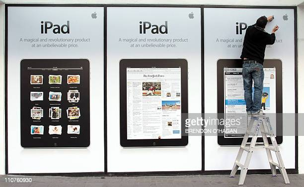 A worker puts up signs for the new iPad before it's launch in New Zealand at a Apple store in Auckland on July 23 2010 The third phase of Apple's...