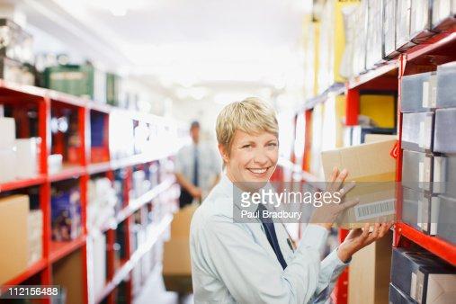 Worker putting box on shelf : Stock Photo