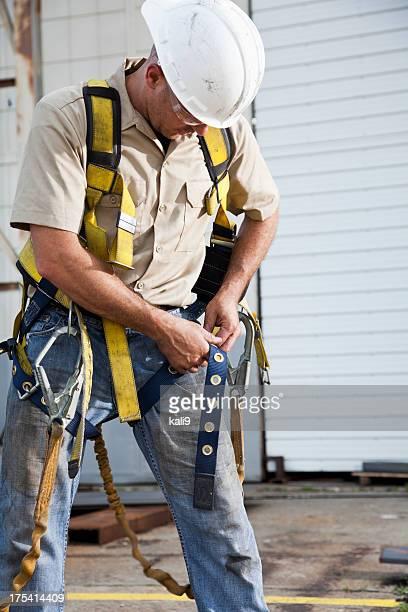 Arbeiter putting auf Sicherheitsgurt