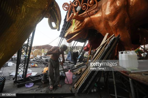 Worker Raimundo Edvan cleans amidst the rubble of the Carnival floats warehouse for the Renascer de Jacarepagua samba school on August 29 2017 in Rio...