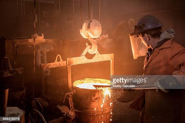 Worker raking molten steel in foundry workshop