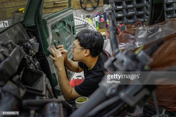 Worker re install door interior at mohenic garage in Paju South Korea A 20yearold beat up Hyundai SUV isn't anyone's idea of a dream car But used...