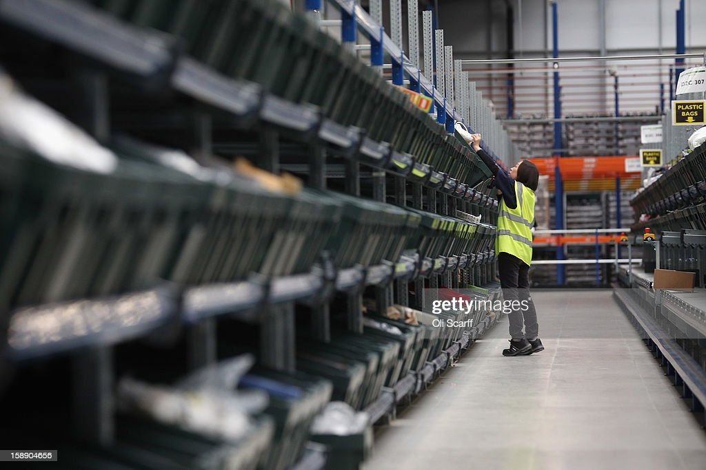 A worker reaches in the giant semi-automated distribution centre where the company's partners process the online orders for the John Lewis department store on January 3, 2013 in Milton Keynes, England. John Lewis has published their sales report for the five weeks prior December 29, 2012 which showed online sales had increased by 44.3 per cent over the same period in 2011. Purchases from their website Johnlewis.com now account for one quarter of all John Lewis business.