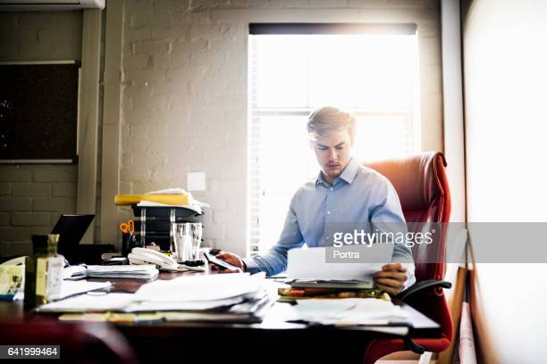 Worker reading document at desk in brewery