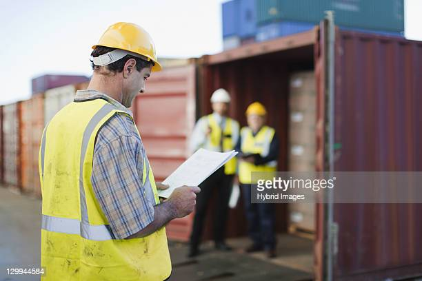 Worker reading in shipping yard