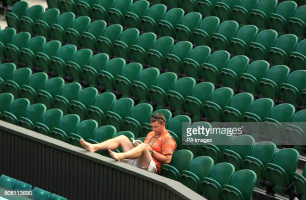 A worker reads a book on Centre Court during Day Six of the 2010 Wimbledon Championships at the All England Lawn Tennis Club Wimbledon