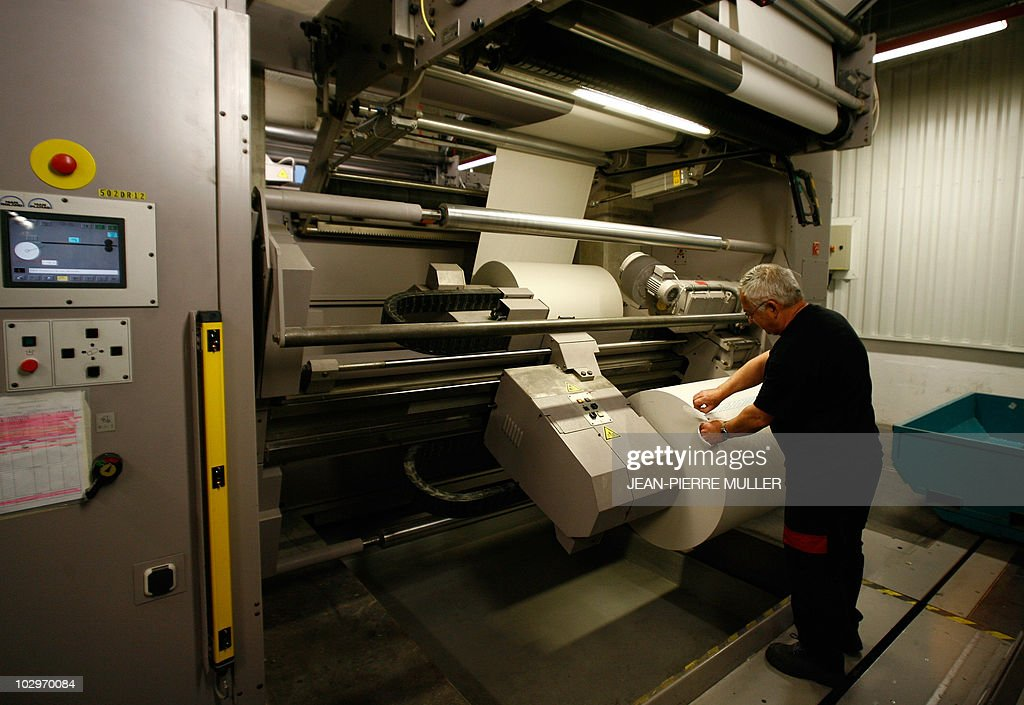 A worker refills a rotary newspaper printing press machine in the basement of the French newspaper Sud-Ouest on February 19, 2008 in Bordeaux, southern France.