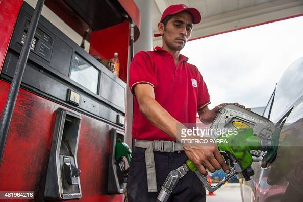 A worker refuels a car at a petrol station in Caracas on January 22 2015 With Venezuela's economy in crisis President Nicolas Maduro on Wednesday...