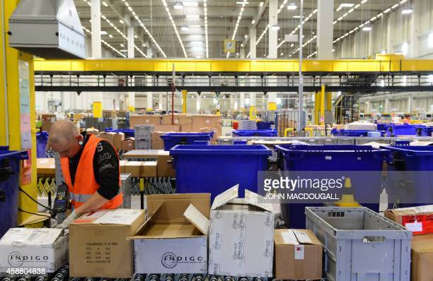 A worker registers incoming products at US online retail giant Amazon's Brieselang logistics center west of Berlin on November 11 2014 The center is...