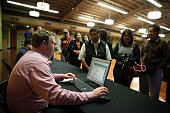 A worker registers job seekers during a job fair at California's Great America theme park on February 6 2015 in Santa Clara California Hundreds of...