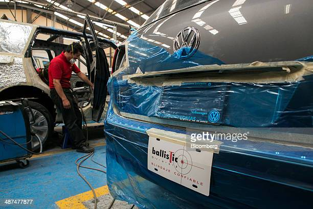A worker reinforces the door of a vehicle at Ballistic Protection Co's armored car workshop in Mexico City Mexico on Tuesday April 29 2014 Mexico's...