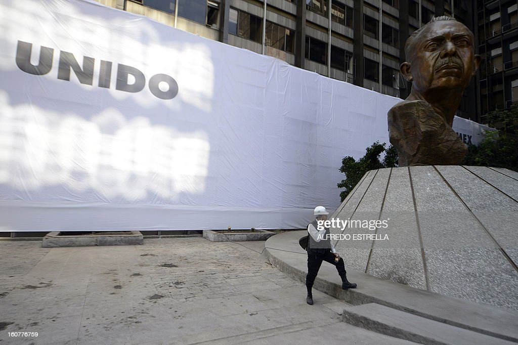 A worker remains outside the damaged building of Mexican state-owned oil giant Pemex, after a blast, in Mexico City on February 5, 2013. A gas build-up caused the explosion that rocked the headquarters of Mexico's state-owned oil firm last week, killing 37 people, officials said Monday, ruling out a bomb attack. The explosion also injured morfe than 120 people. AFP PHOTO/Alredo Estrella
