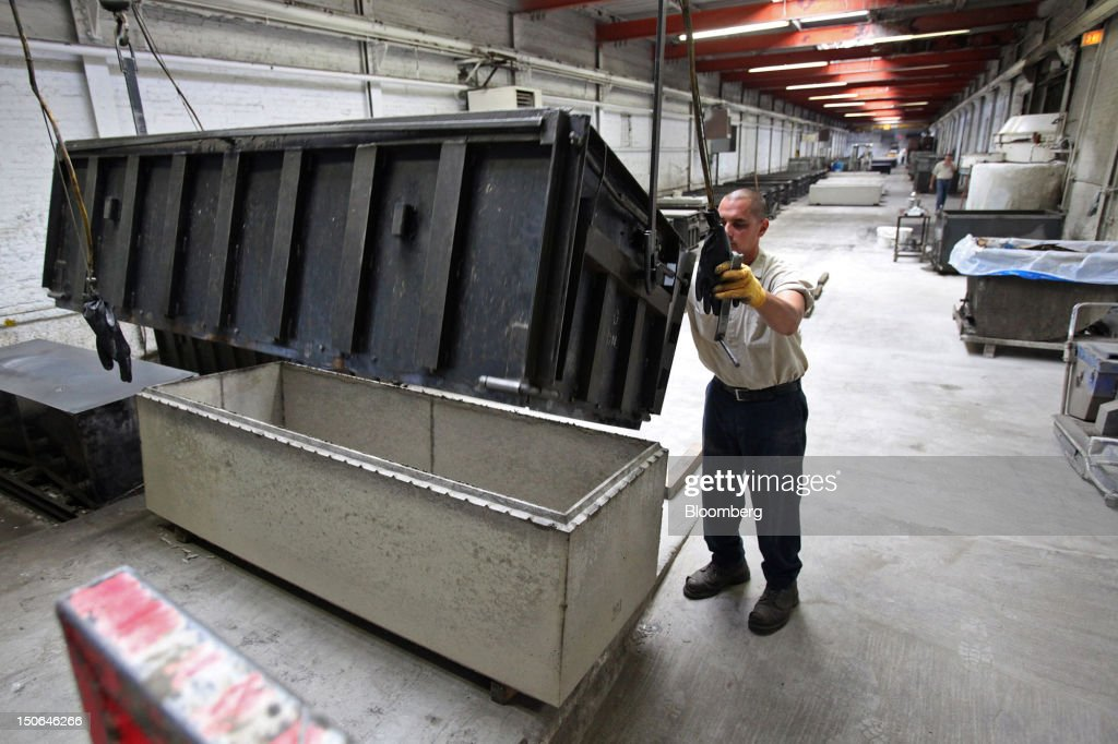 A worker removes a concrete form from a burial vault at the American Wilbert Vault Corp. manufacturing facility in Des Plaines, Illinois, U.S., on Thursday, Aug. 23, 2012. Several U.S. Presidents including John F. Kennedy and Ronald Reagan, and other famous people including Al Capone, Louis Armstrong, Elvis Presley and Frank Sinatra are buried in American Wilbert burial vaults, according to the company. The U.S. Census Bureau is expected to release data on orders for durable goods on Aug. 24. Photographer: Tim Boyle/Bloomberg via Getty Images