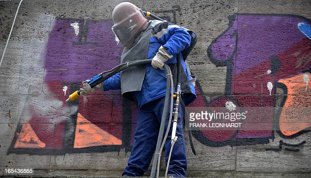 A worker removes a graffiti with a sandblaster from a wall on April 4 2013 in Munich southern Germany AFP PHOTO / FRANK LEONHARDT GERMANY