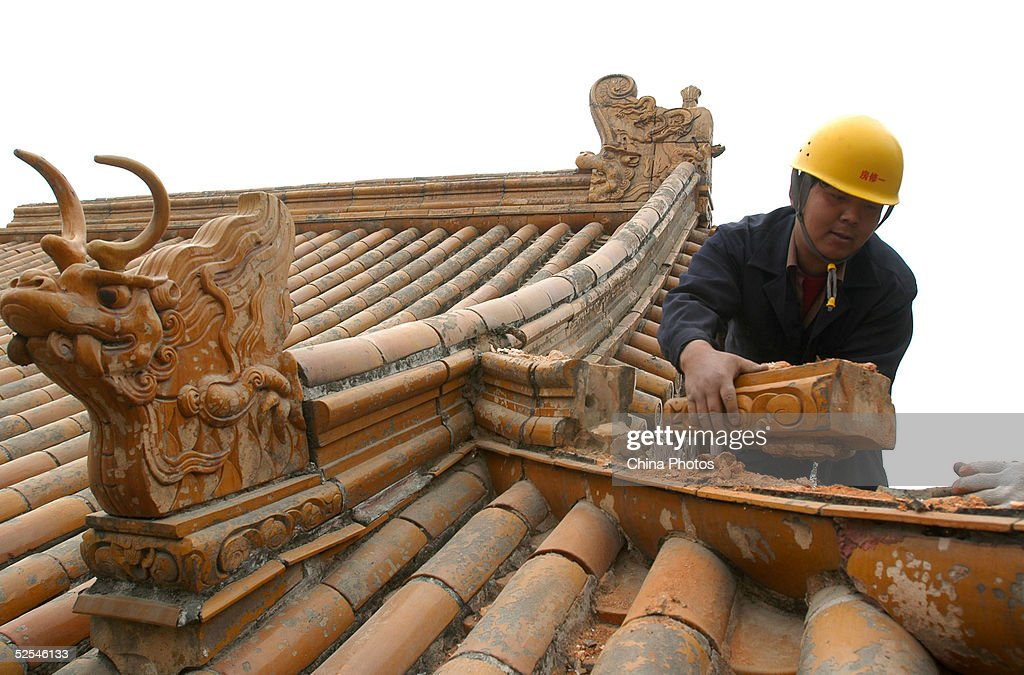 A worker removes a tile of a building at the Summer Palace on March 31, 2005 in Beijing, China.The best-kept existing royal garden is under a heavy restoration in 53 years, which is scheduled to be completed next year. The Summer Palace, first built in 1750, is the second largest imperial garden in ancient China. Beijing's legislature has passed a long-awaited regulation, the 'Beijing Regulation for Historical and Cultural City Protection' to protect its over 3,500 listed heritage and sites of cultural value.