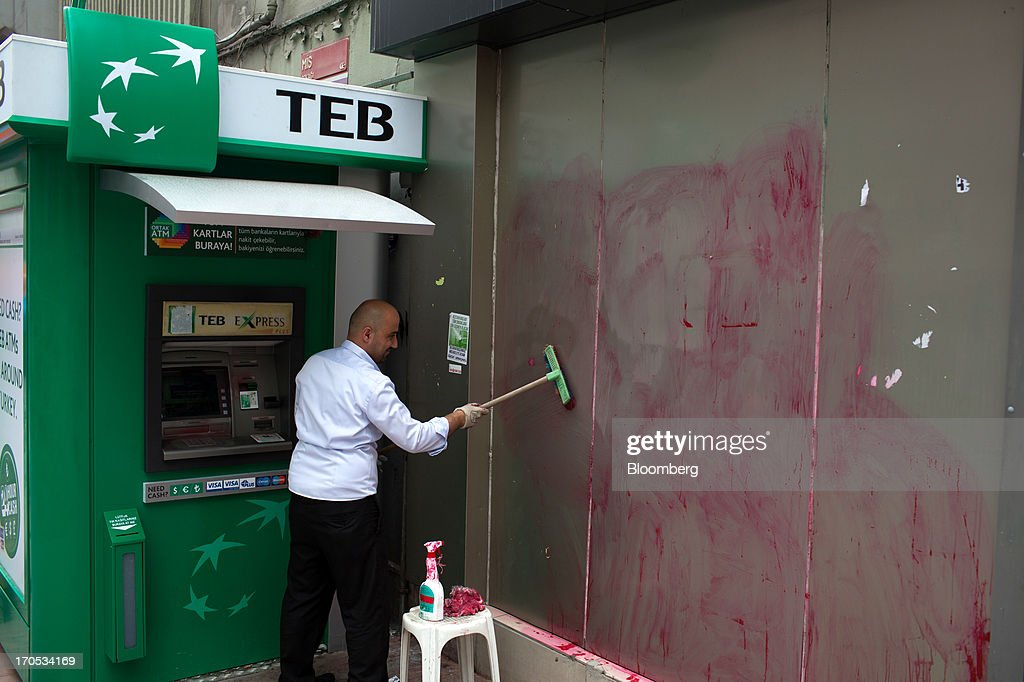 A worker removes anti-government graffiti from a wall beside a Turk Ekonomi Bankasi AS automated teller machine (ATM) near Taksim Square in Istanbul, Turkey, on Thursday, June 13, 2013. The law forbids the sale of alcohol at night and near schools and mosques, going against the secular traditions of the Muslim-majority country of 74 million, where many people drink and women often choose not to cover their hair. Photographer: Lam Yik Fei/Bloomberg via Getty Images