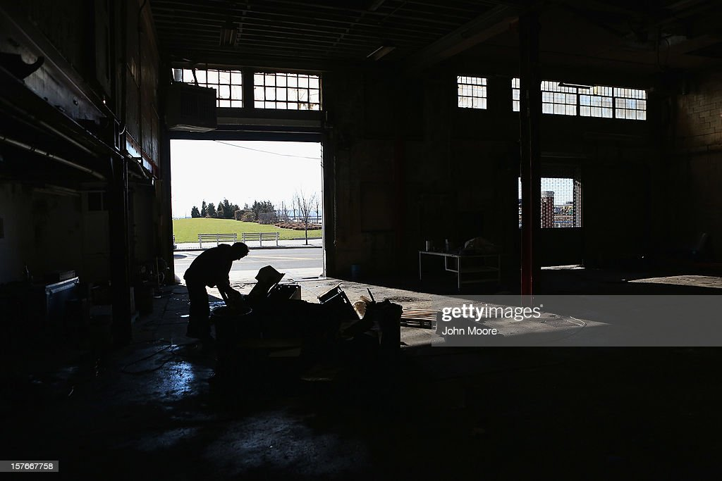 A worker removes debris from a flood-damaged auto repair shop in the Red Hook neighborhood of Brooklyn on December 5, 2012 in New York City. More than a month after superstorm Sandy flooded the area, many homes remain vacant and businesses have been slow to reopen in the neighborhood.