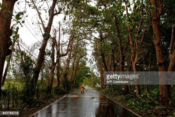 A worker removes debris from a road with a gas powered blower in the aftermath of Hurricane Irma in Rio Grande Puerto Rico on September 7 2017 One of...