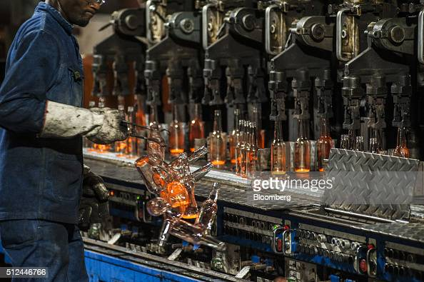 A worker removes hot glass bottles from the molding line at the Nampak Ltd manufacturing plant in Roodekop South Africa on Friday Feb 26 2016 Already...