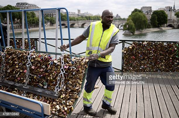 A worker removes 'love padlocks' attached on the railings of the Pont des Arts bridge in Paris on June 1 2015 Started by tourists in Paris in 2008...