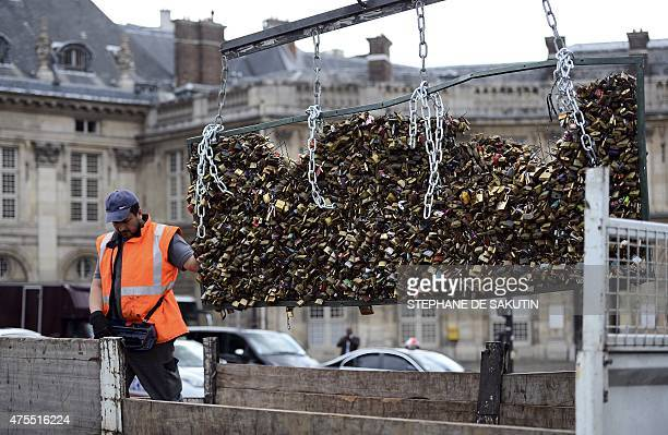 A worker removes love padlocks attached on the railings of the Pont des Arts on June 1 2015 in Paris Started by tourists in Paris in 2008 the love...