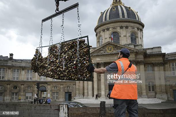 A worker removes 'love padlocks' attached on the railings of the Pont des Arts on June 1 2015 in Paris Started by tourists in Paris in 2008 the love...
