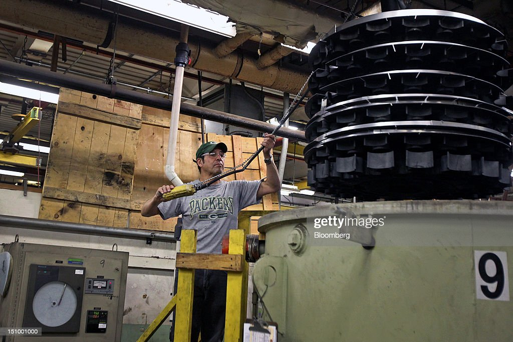 A worker removes steel coils for manufacturing band saw blades from a large furnace at DoALL Company's Contour Saws Inc. facility in Des Plaines, Illinois, U.S., on Tuesday, Aug. 28, 2012. The U.S. Census Bureau is scheduled to release factory orders data on Aug. 31. Photographer: Tim Boyle/Bloomberg via Getty Images