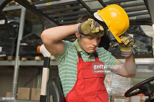 Worker removing hard hat