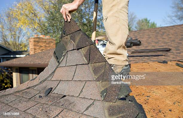 Worker Removing Old Roof Shingles for Replacement