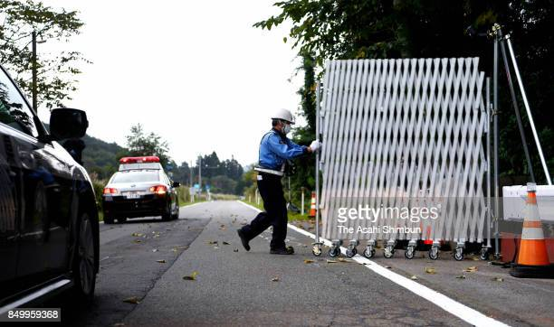 A worker reopens a section of National Route 114 that runs through a 'difficulttoreturn' zone on September 20 2017 in Namie Fukushima Japan A...