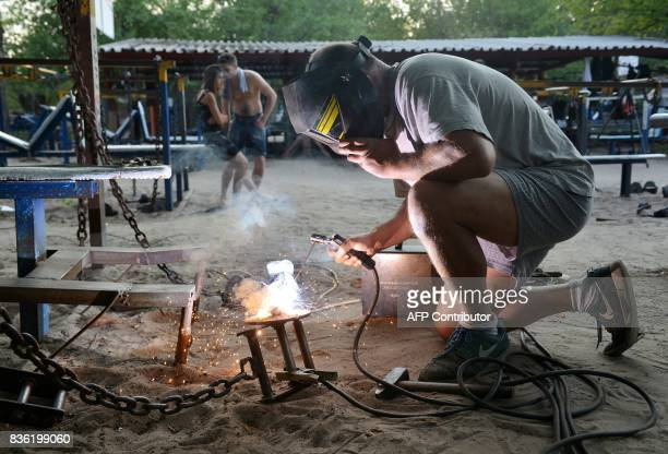 A worker repairs dumbbells on August 18 2017 at an open air gym in Ukraine's capital Kiev Foundedin the 1970s the busy open air gym called Kachalka...
